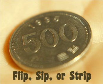 A flip a coin New Year's game called: Flip, sip or strip! Picture of a coin the palm of a hand.