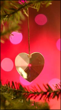 Warm Christmas quotes on love: Golden Christmas heart hanging on Christmas tree.