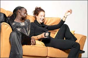 Funny birthday words: Two girls having a laugh in a sofa.