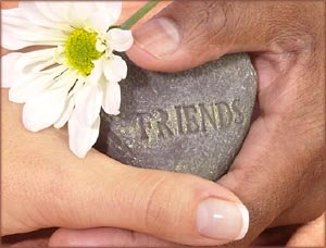 Thank you quotes: Two hands holding a stone with friends written on it and flower next to it.