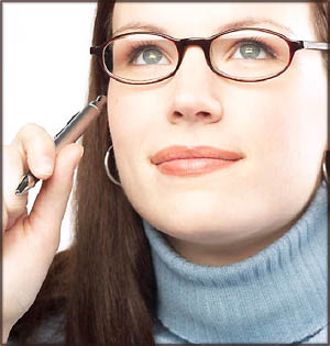 Pensive woman thinking about writing happy birthday messages while holding a pen up to her face.