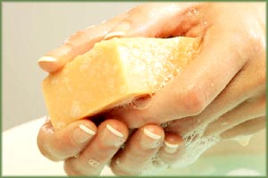 Orange soap bar in woman's hands.