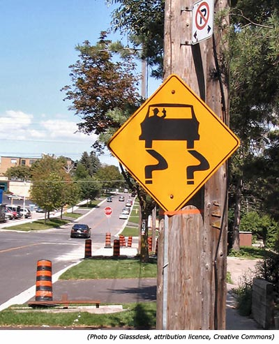 Funny road signs: A yellow sign with a drunk and inside a car and with a bottle in his hand.