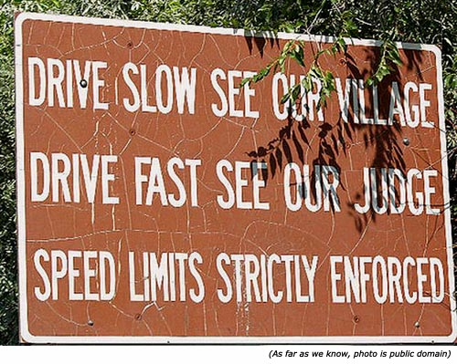Hilarious traffic sign: A funny town sign saying: Drive slow see our village! Drive fast see our judge! Speed limits strictly enforced!