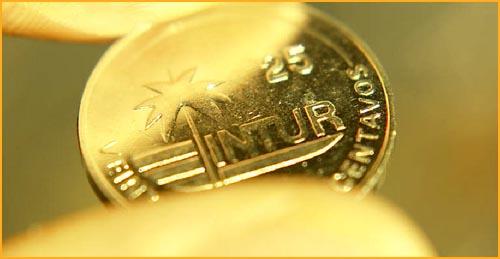 Gold coin held between fingers.