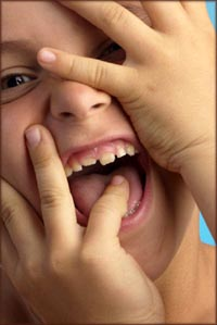 Little boy laughing while covering his face.