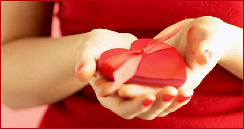 Love hearts photo: Picture of woman holding a red heart in both her hands.