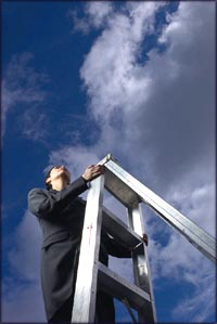 The sky is the limit: Woman climbing ladder with blue sky and clouds in the background.
