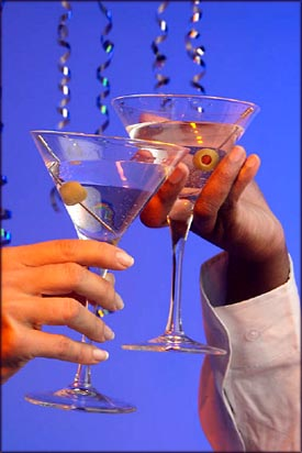 New Year Greetings and Toasts: Hands holding martinis and toasting to a happy new year.