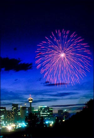 Pink firework on city night skyline.