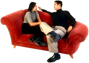 Talk about your resolutions for New Year with a loved one: Young couple talking in sofa.