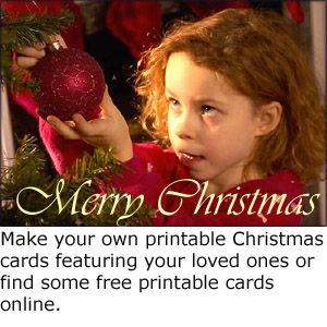 Homemade photo Christmas greeting card: Make your own printable christmas cards: Little girl hanging up Christmas decorations on Christmas tree.
