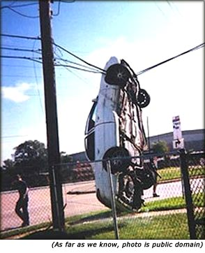 Funny car accident. Picture of car hanging in telephone wires.