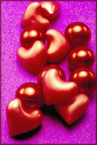Lots of red plastic hearts on purple background. Short love poems inspiration.