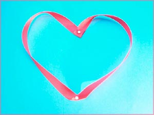 Being thankful opens up your heart: Pink heart ribbon on blue background.