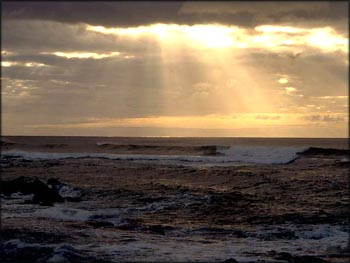 Feeling Gratitude: Sunshine penetrating dark clouds over the sea.