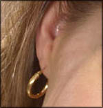 Woman's ear and golden earring.