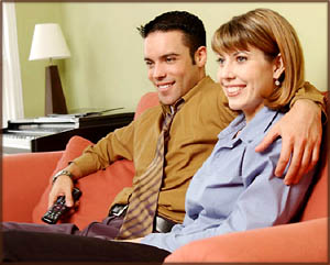 Valentine ideas: Couple sitting in sofa watching a movie.