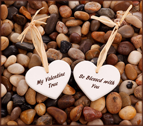 Free Valentines to print: Photo of two small white hearts with Valentines poems lying on small pebbles.