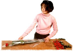 Woman florist arranging roses for a Valentine gift.