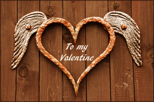 Beautiful Valentine Pictures: Photo of iron heart with white wings hanging on brown wooden boards.