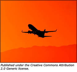 Picture of a plane leaving in the orange sunset.