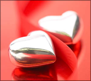Two silver hearts on red background.