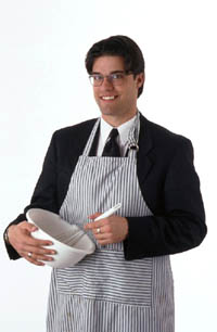 Valentine idea: man in suit and apron cooking, stirring in a bowl.