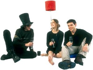 Three people having a birthday party on the floor.