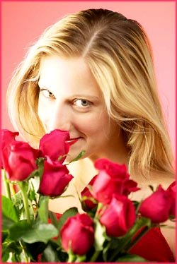 Happy birthday messages: Woman smelling red roses.
