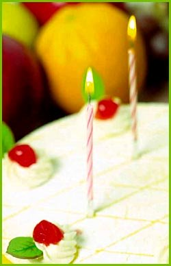 Close up photo of white birthday cake and two candles.