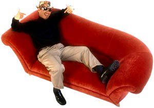 Inspirational love stories: Happy man relaxing in a red sofa.