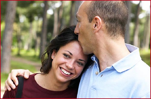 Man kissing woman's forehead. Happy woman smiling.