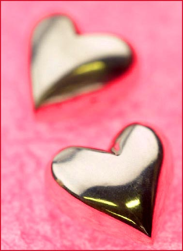 Love: picture of two silver hearts on pink velvet.