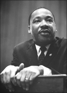 Photo of Martin Luther King leaning foreward on pulpit.