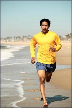 Motivation: man running on the beach by the water.