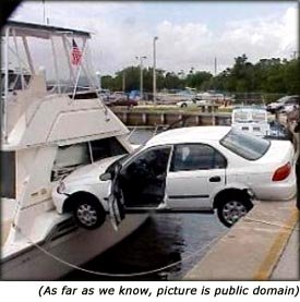 Funny picture of car accident. Car crashing into yacht.