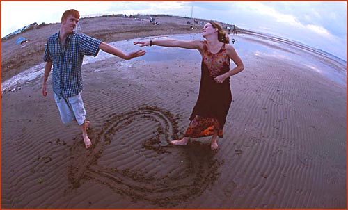 Teenagers in Love: Young happy couple at the beach holding hands. Heart drawing in the sand.