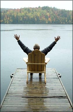 Being thankful for life: Man sitting in a chair on a small bridge with his arms out to the side.