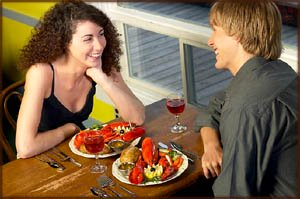 Ideas for dinner: Couple eating lobster in a cosy restaurant.
