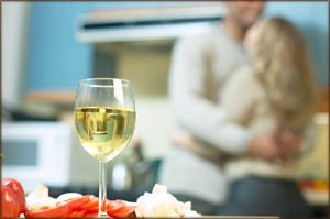 Valentines Day idea for homecooking. Photo of a glass of white wine in kitchen and a couple hugging in the background.